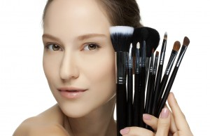 Portrait of the beautiful woman with make-up brushes.