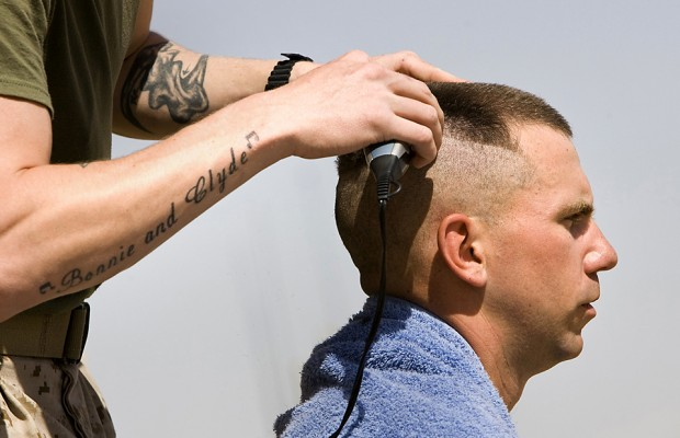 A U.S. Marine gives his comrade a haircut at Camp Leatherneck in Helmand province